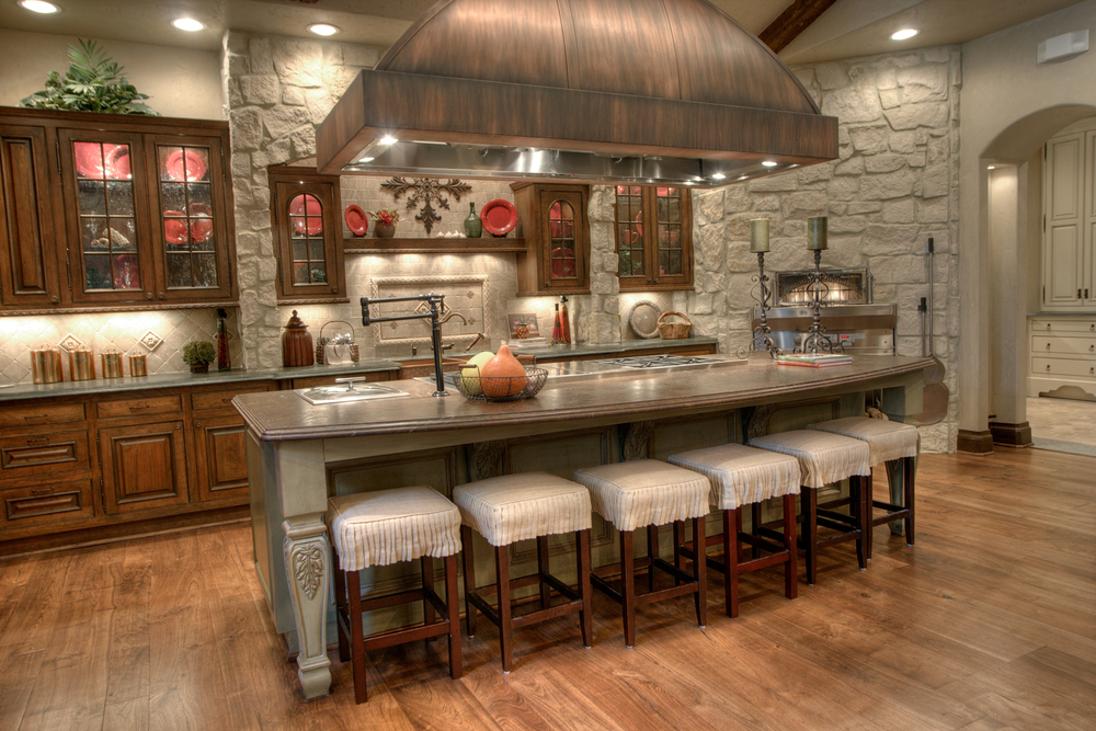 Traditional    Traditional rustic kitchen features stained cabinets, glass door fronts, contrasting oversized island and customized vent for stunning results.  Project location:  Houston, TX