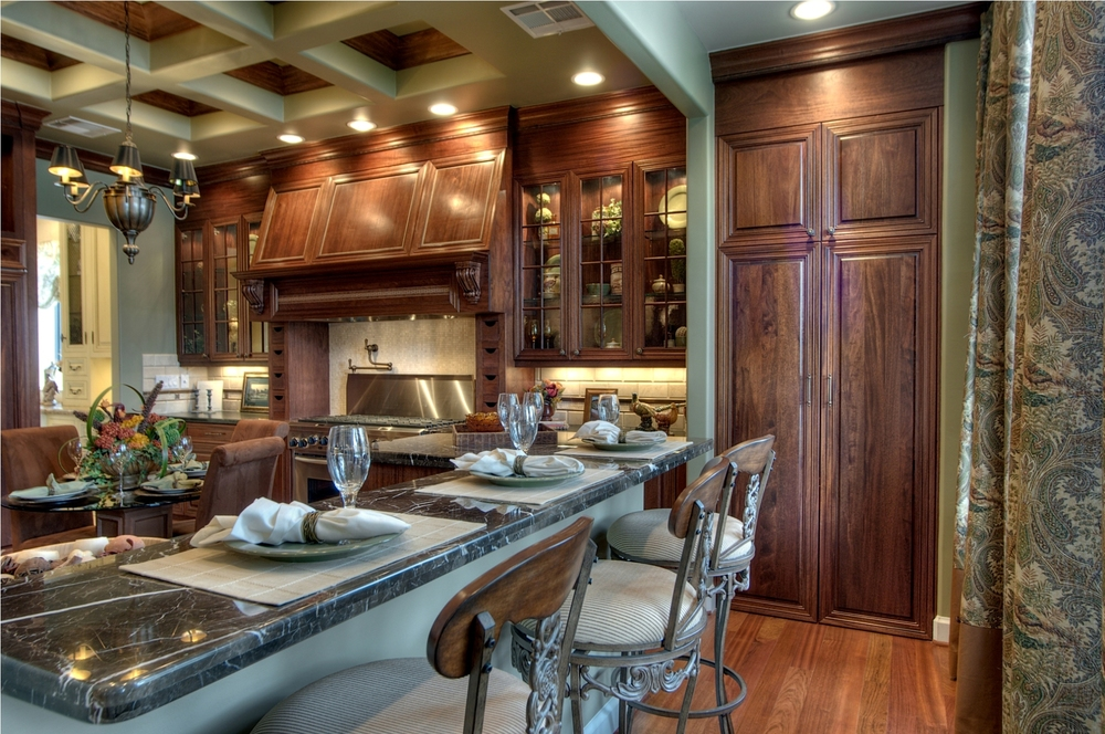 Traditional   This elegant traditional kitchen features mahogany cabinets with glass front doors and custom vent.    Project location:  Houston, TX