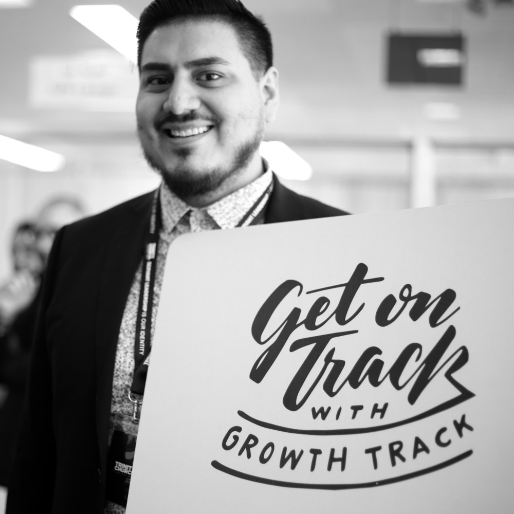 "A young adult male holds a sign reading ""Growth Track."""