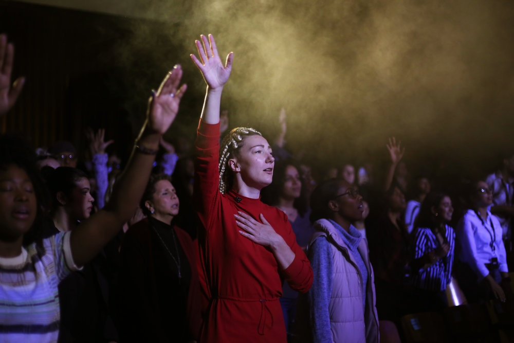 A woman raises her hand during worship.