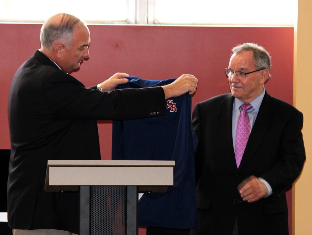 Ernie Mrozek '71 presents Mayor Daley with St. Rita Mustangs shirt.