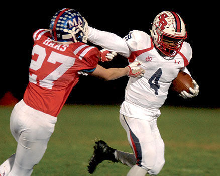 St. Rita running back Shaun Rule (4) stiff arms a Marmion defender.