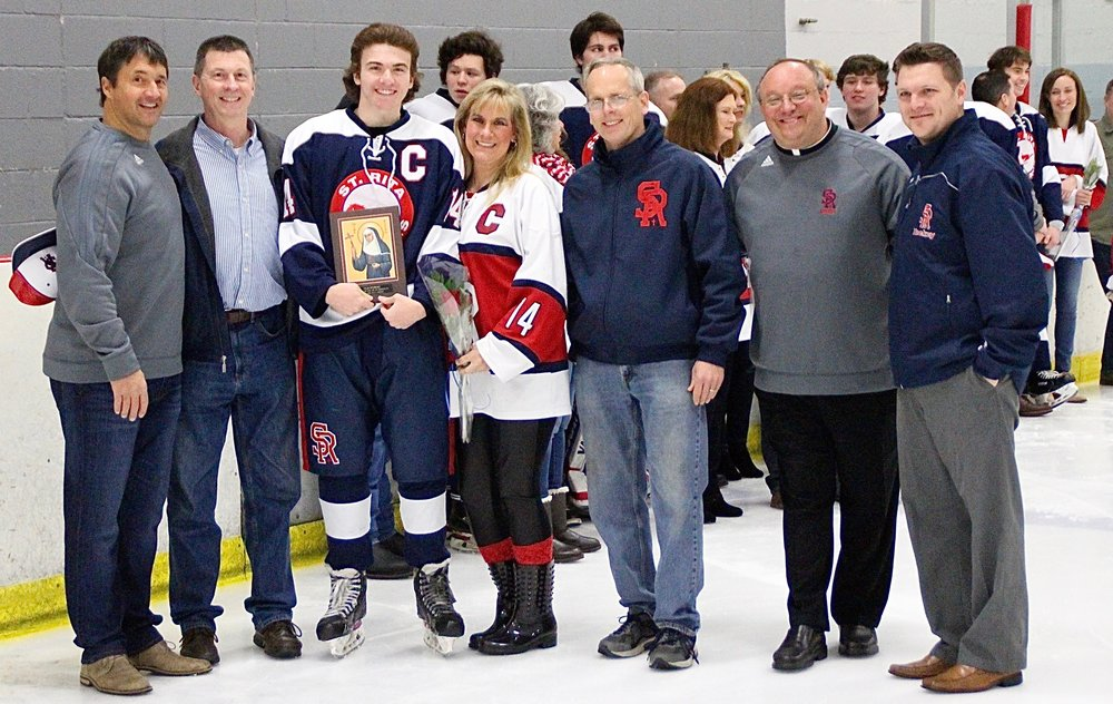 Colan Fitzgerald and parents Tom and Linda Fitzgerald gather for a pre-game ceremony with St. Rita Administrators and Head Coach Brian Coleman '99 on St. Rita Hockey Senior Night.