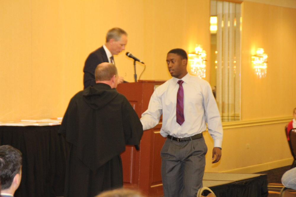 University of Illinois-bound Marc Mondesir is congratulated by Fr. Paul Galetto, Ph.D., O.S.A. at the 27th Annual St. Rita Academic Awards Banquet.