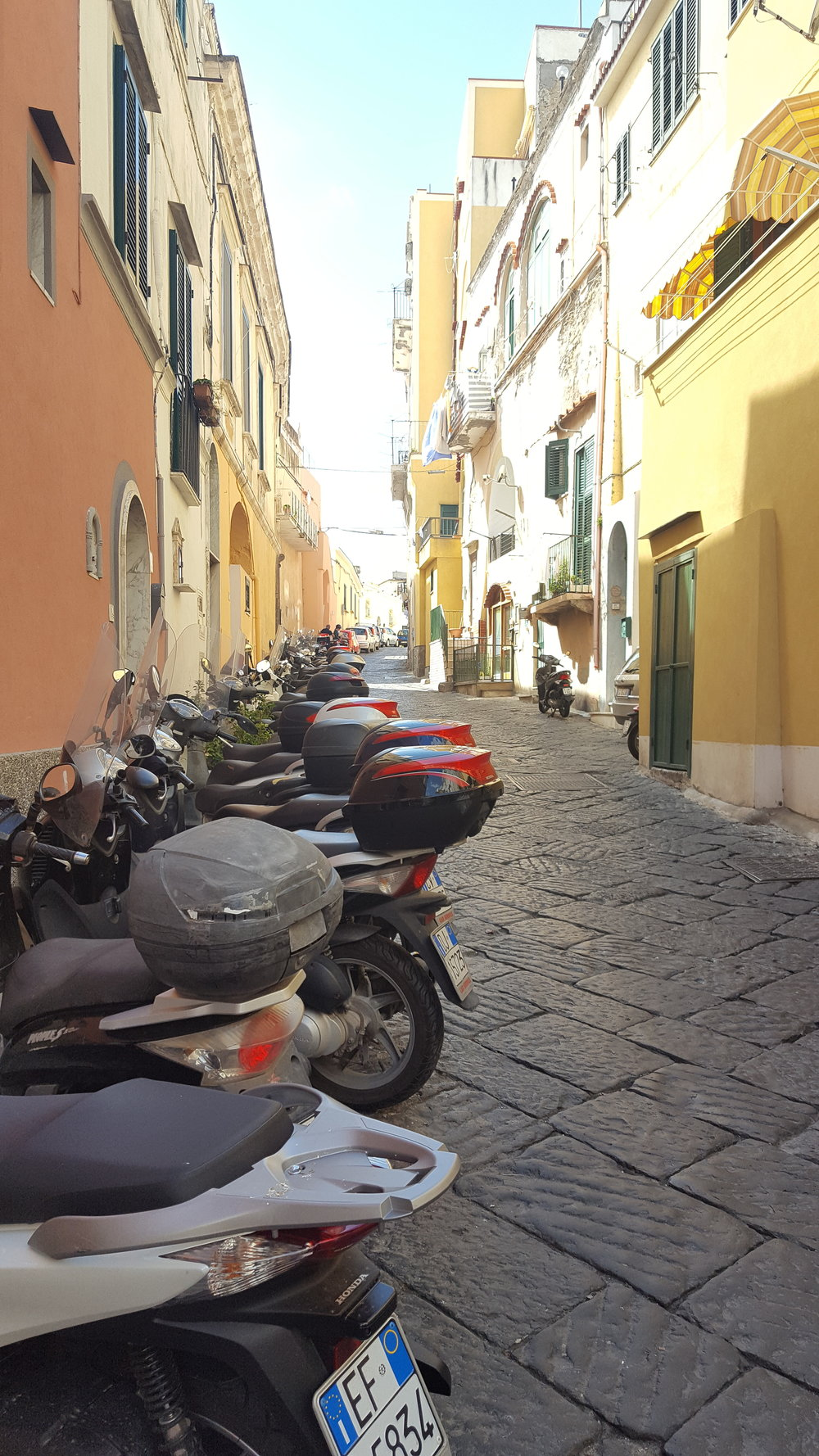A typical street in Procida - packed with scooters.