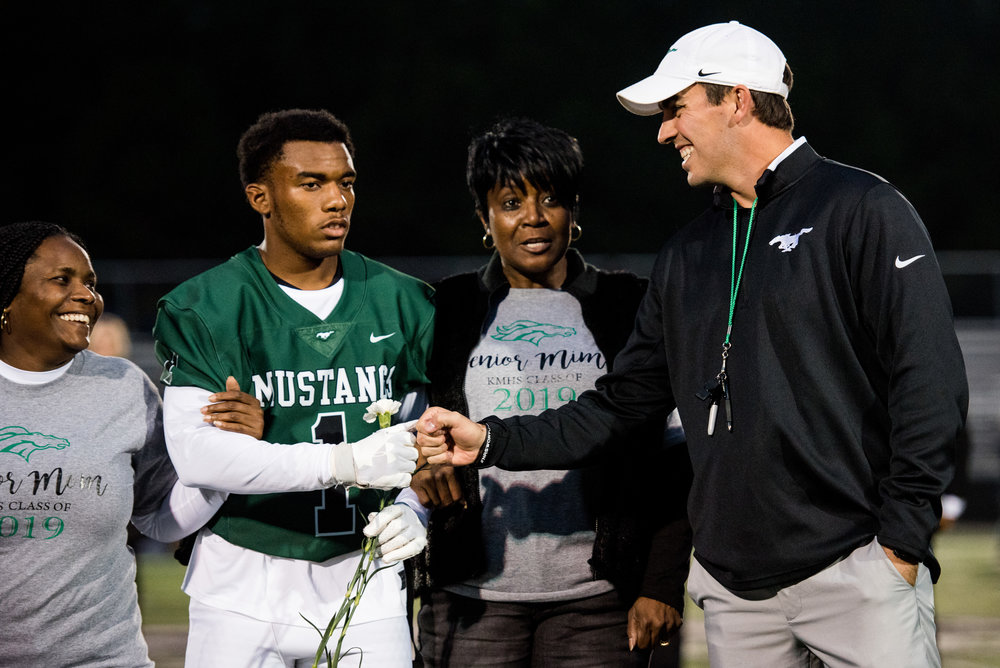Terrence Chisley (1) fist bumps head coach Caleb Carmean as he's recognized during senior night prior to Friday's matchup against North Paulding High School in Kennesaw, Ga., Friday, Oct. 26, 2018. The Mustangs fell to the Wolfpack 41-21. (Photo by Cory Hancock)