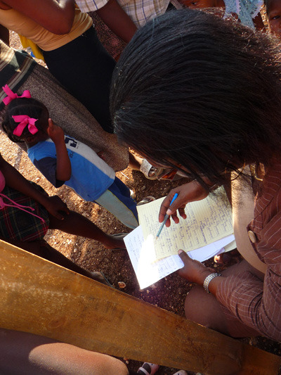Jocelyne Pierre goes through the list compiled by the tent camp's committee, as she screens 4 and 5 year olds.