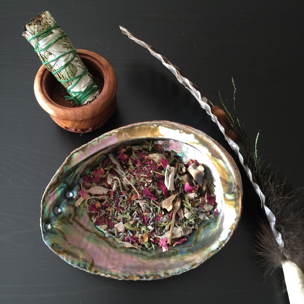 ...a traditional white buffalo sage smudge stick (left), a loose leaf smudge mix with rose, cedar & sage in a shell burning pot (middle), and a traditional eagle featherwafting stick (right).
