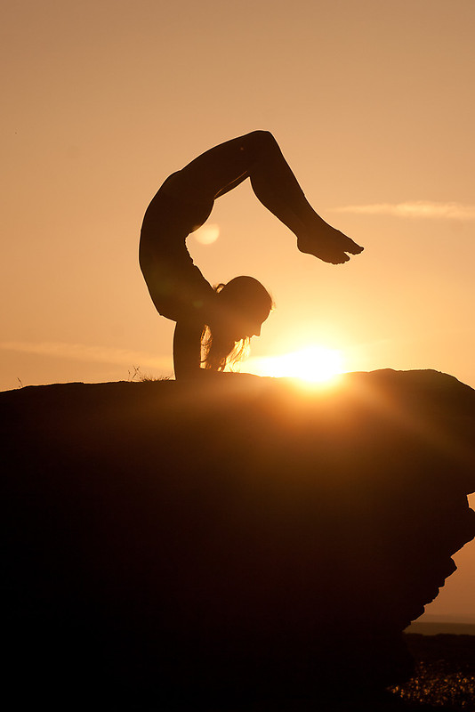 Vrschikasana (Scorpion Pose) at sunset...Vrschikasana,a very challenging pose (take your time with this one and have an instructor guide/ help you! This is one that you build up to!), isthe perfect asana for Solstice for the way itopens theheart allowing all that beautiful light to flood inand because it is such a challenging inversion, itrequires that you move beyond ego and embrace possibility that we otherwise may not believe exists. So truly, the light mustconquerthe dark for thispose to be available; don't you just love that?!?! In my practice,I am very much awork in progress withVrschikasana, building up to with through thefoundationPincha Mayurasana (Forearm Balance). Photo Credit: Red Bubble
