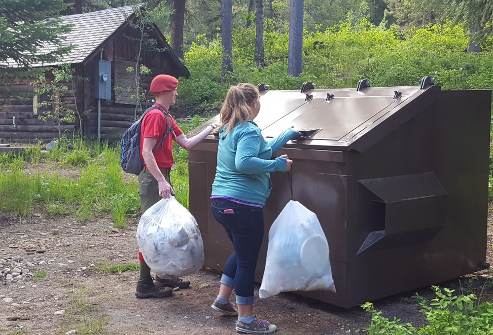 Kids using the new bear-resistant dumpsters at Treasure Mountain Scout Camp. To keep scouts safe and bears wild, Greater Yellowstone Coalition and the Boy Scouts pooled their funds to buy new dumpsters and 20 new bear boxes for the 75-acre camp outside Alta, Wyo. (Photo Greater Yellowstone Coalition.)