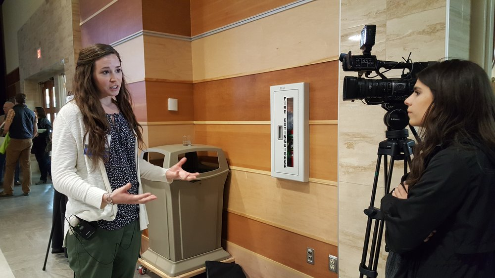 GYC's Special Projects Organizer Brooke Regan gives a recap of the symposium to a local news reporter on Tuesday. (Photo: GYC.)