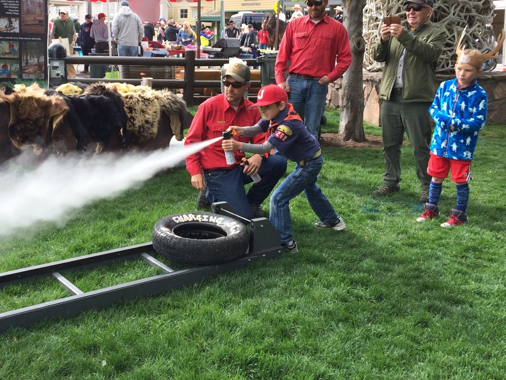 A poised and confident Boy Scout practicing with inert bear spray at ElkFest in Jackson. (Photo GYC.)