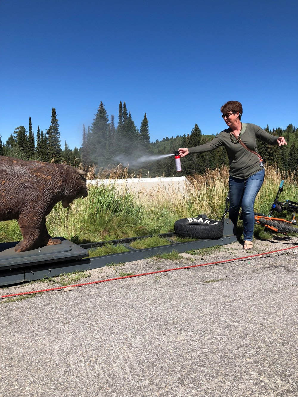 Testing her quick-draw skills with the Charger. We brought this mechanical charging bear to an annual mountain bike festival in Teton Valley, Idaho. (Photo GYC.)