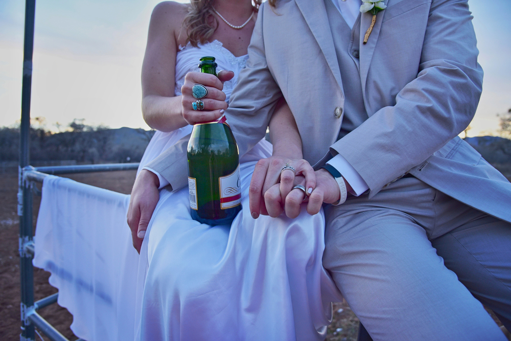 Weddings-Boho-Arizona-Bride-Groom-Rings-Hands-Champagne_Carly-Carpenter.jpg