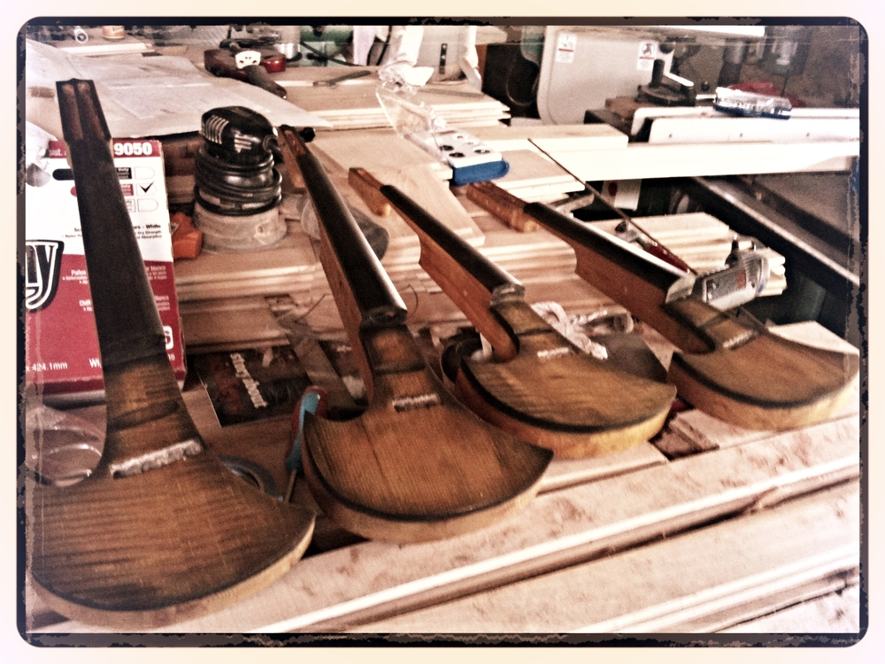 Four of Kyle's electric violins during the construction process
