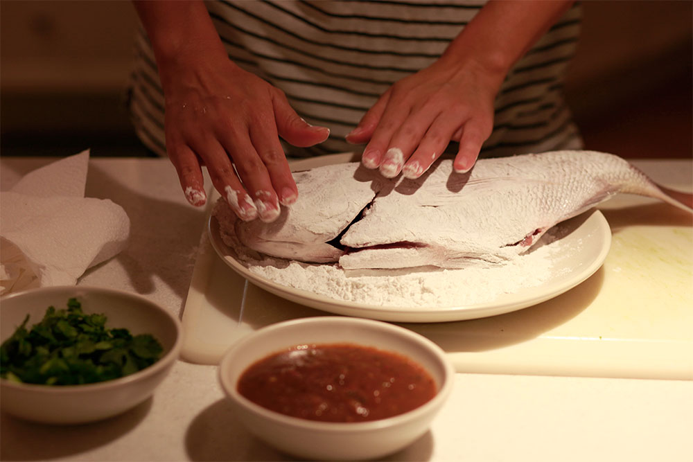 slit the fish and dust generously with rice flour. make sure to get into all the crevices.