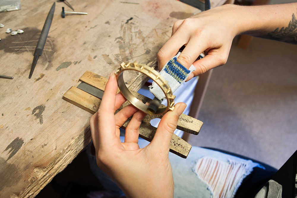 A bangle from Fortitude is carefully sanded by hand.