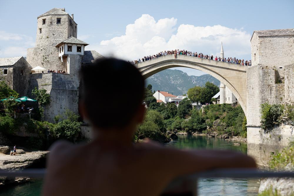 Boy watching from a distance as a diver prepares to take a jump for tourists from the bridge.     Dječak iz daljine gleda skakača koji se sprema za turiste izvesti atraktivan skok u rijeku Neretvu sa Starog mosta u Mostaru.