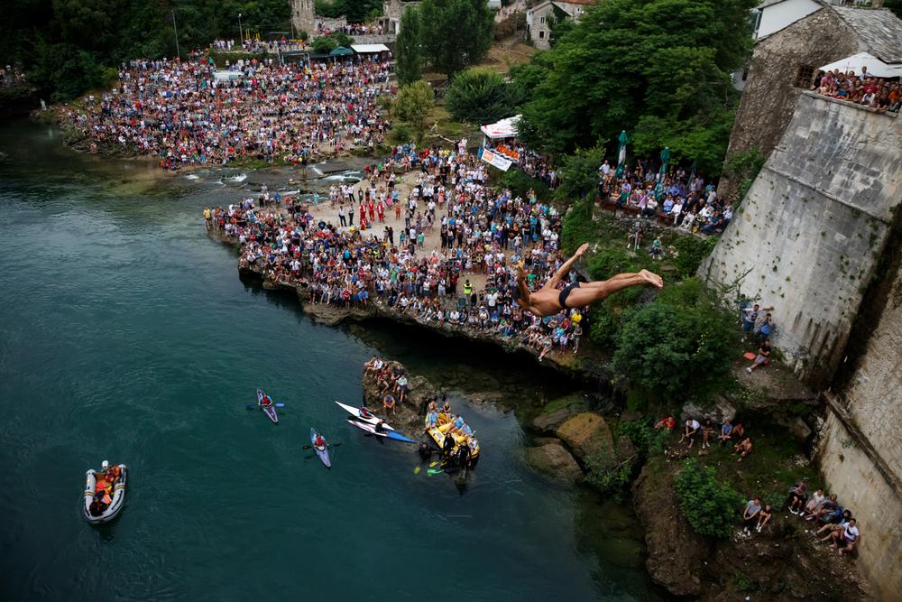 """Man executing the Mostar Swallow, a headfirst dive into the Neretva. """"When you take a dive from the Old Bridge, you've joined the ranks of the bold."""" -Emir Balić, the Swallow of Mostar.     Muškarac izvodi mostarsku lastu ili skok na glavu u rijeku Neretvu u Mostaru. """"Kad se skoči sa Starog mosta, tada se upisuje u društvo odvažnih."""" - Emir Balić, mostarska lasta."""
