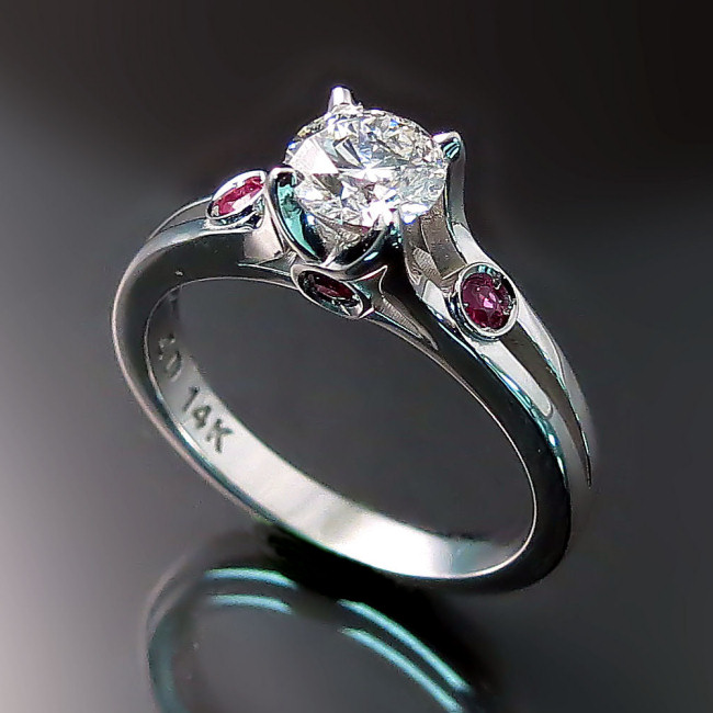 This engagement ring was commissioned by a client wishing to incorporate rubies from a ring inherited from a grandparent. Old and new came together beautifully in this contemporary custom made engagement ring.