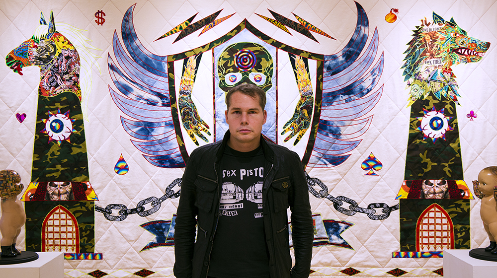 Shepard Fairey in front of work by Ben Venom