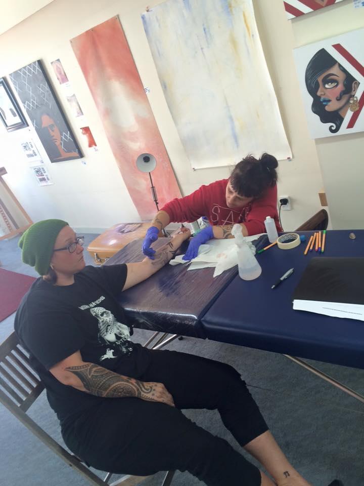 Moko artist Sian Montgomery-Neutze tattooing clay artist Stevei Houkamau.