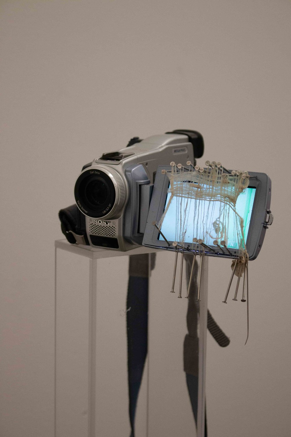 """""""Untitled Wormhole 06"""", Sony MiniDV Camcorder, Stainless Steel Nails, Exposed Silk (2 Silkworm Cocoons exposed to YouTube search algorithm, """"9/11 videos"""" played continually for 10 days), Needle , Needle. 4"""" x 6"""" x 8"""" (Inches). 2018."""