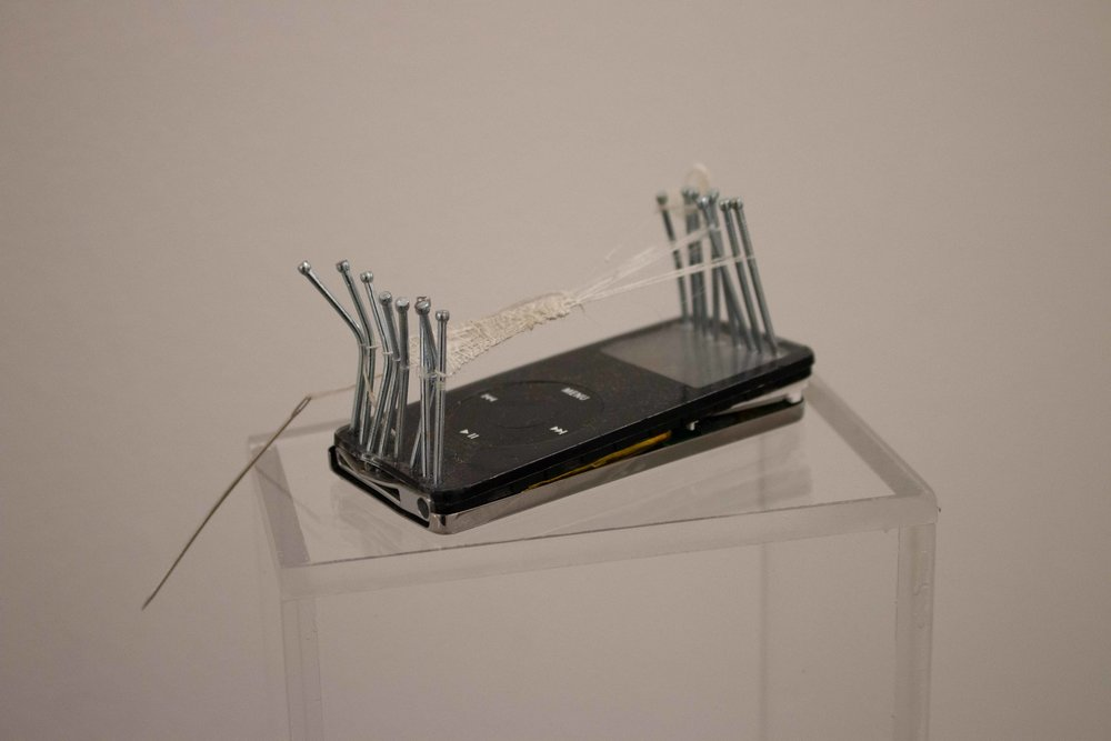 """""""Untitled Wormhole 01"""", iPod Nano (1st Generation), Stainless Steel Nails, Exposed Silk (2 Silkworm Cocoons exposed to YouTube search algorithm, """"Aladdin"""" played continually for 10 days) , Needle. 3.5"""" x 1.6"""" x 2"""" (Inches). 2018."""