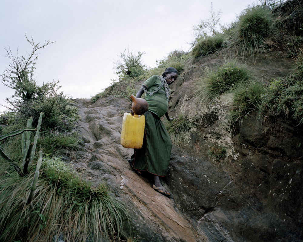Uchiya Nallo, 8 months pregnant, gathering water to make the beer for the village men to celebrate her birth. Konso Region, Ethiopia, 2013.