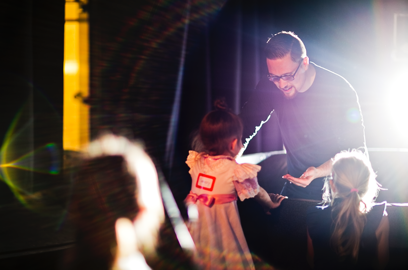 Pastor Kyle explaining baptism to nearby kids during Rainier Valley Church's 2019 Easter Sunday service