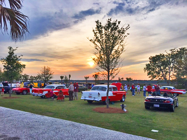 old cars on display outside at sunset