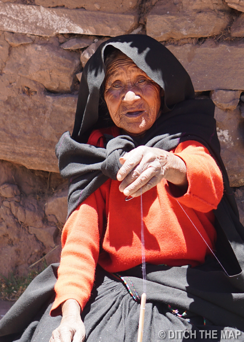 A woman spinning yarn on Taquile Island in Lake Titicaca, Peru