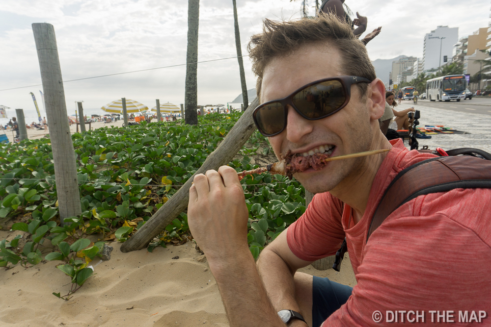 Snacking on some street meat along Ipanema Beach in Rio de Janeiro, Brazil
