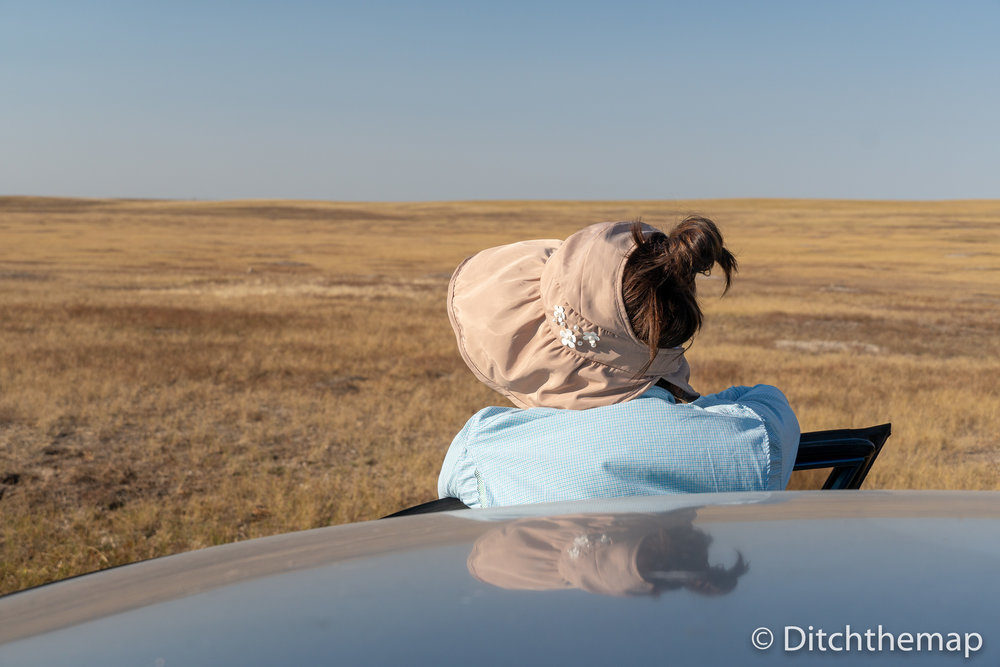 Girl with sun visor standing near car and looking over grassland