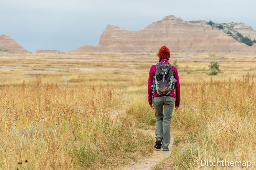 Girl Walking Down Gravel Path into Mountains of Badland National