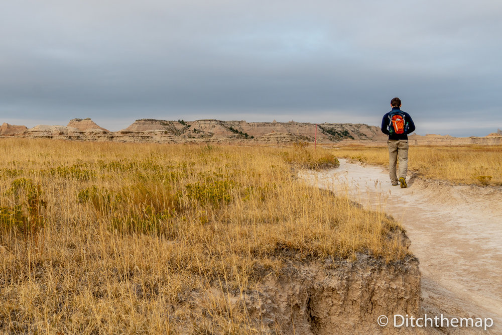 Man Walking Down Path into Panoramic View of Badlands Geological