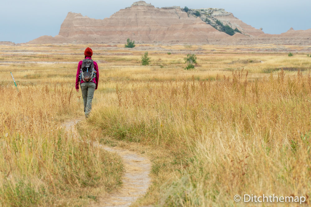 Girl Walking Down Gravel Path into Mountains in the Badlands