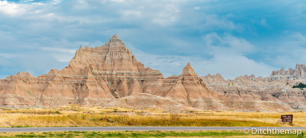 Panoramic View of Badlands Geological Features with Welcome sign