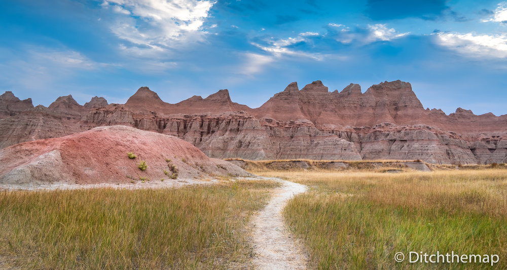 Panoramic View of Badlands Geological Features with prarie in fo