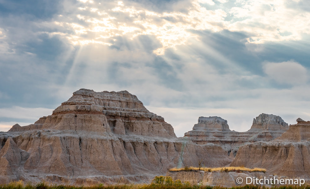 Panoramic View of Badlands Geological Features along with rays o