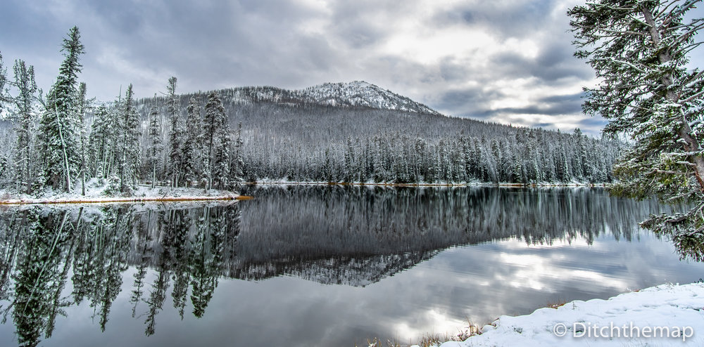 Light snow covered trees and mountain with reflection on lake