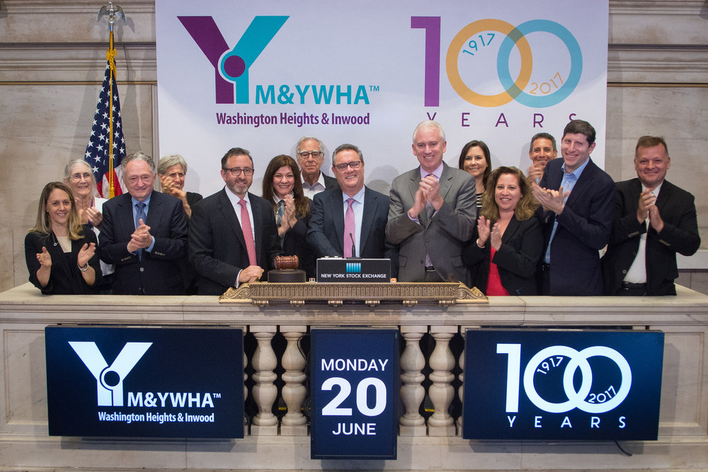 100 Years Logo Featured at the New York Stock Exchange - To commemorate the Y's centennial, the New York Stock Exchange invited us to ring their iconic bell. On June 20, 2016 a group of board members and staff gathered on the NYSE's balcony and trading floor to cheer as CEO Martin Englisher rang the Closing Bell. The 100 Year Anniversary Logo, created by Studio By Shera, was prominently featured on backdrops, banners, and screens throughout the event.
