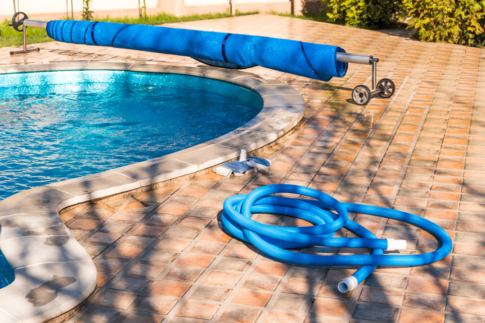 pool cover and hose by pool in backyard