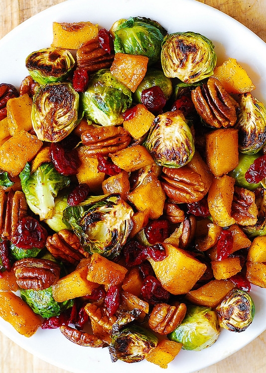 ROASTED BRUSSELS SPROUTS, CINNAMON, BUTTERNUT SQUASH, PECANS, AND CRANBERRIES  INGREDIENTS Roasted Brussels Sprouts: 3 cups Brussels sprouts, ends trimmed, yellow leaves removed 3 tablespoons olive oil Salt, to taste Roasted Butternut Squash: 1 and ½ pound butternut squash, peeled, seeded, and cubed into 1-inch cubes (Yields about 4 cups of uncooked cubed butternut squash) 2 tablespoons olive oil 3 tablespoons maple syrup ½ teaspoon ground cinnamon Other Ingredients: 2 cups pecan halves 1 cup dried cranberries 2-4 tablespoons maple syrup (optional)  INSTRUCTIONS Roasted Brussels sprouts: Preheat oven to 400 F. Lightly grease the foil-lined baking sheet with 1 tablespoon of olive oil. Make sure Brussels sprouts have trimmed ends and yellow leaves are removed. Then, slice all Brussels sprouts in half. In a medium bowl, combine halved Brussels sprouts, 2 tablespoons of olive oil, salt (to taste), and toss to combine. Place onto a foil-lined baking sheet, cut side down, and roast in the oven at 400 F for about 20-25 minutes. During the last 5-10 minutes of roasting, turn them over for even browning, the cut sides should be nicely and partially charred but not blackened (see my photos). Roasted butternut squash: Preheat oven to 400 F. Lightly grease the foil-lined baking sheet with 1 tablespoon of olive oil. In a medium bowl, combine cubed butternut squash (peeled and seeded),1 tablespoon of olive oil, maple syrup, and cinnamon, and toss to mix. Place butternut squash in a single layer on the baking sheet. Bake for 20-25 minutes, turning once half-way through baking, until softened. _Note:_You can roast both Brussels sprouts and butternut squash on 2 separate baking sheets at the same time, on the same rack in the oven – that's what I did. Assembly: In a large bowl, combine roasted Brussels sprouts, roasted butternut squash, pecans, and cranberries, and mix to combine. (OPTIONAL): For more sweetness, add 2 or 4 tablespoons of maple syrup, if desired – do not add all mapl
