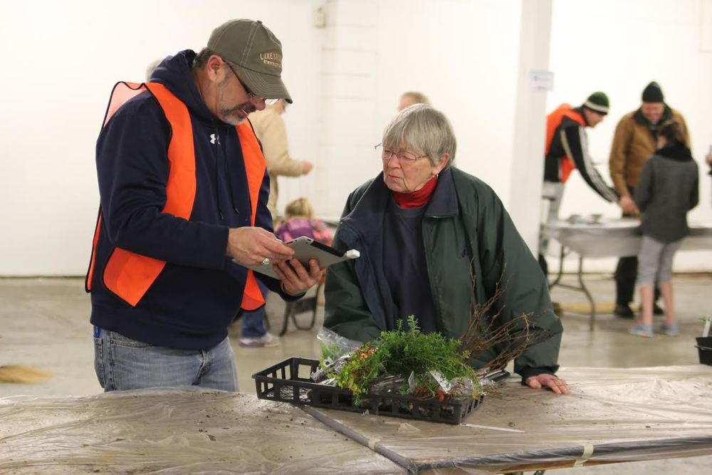 Photo of Board Chair, Mark Craven, and a plant sale customer