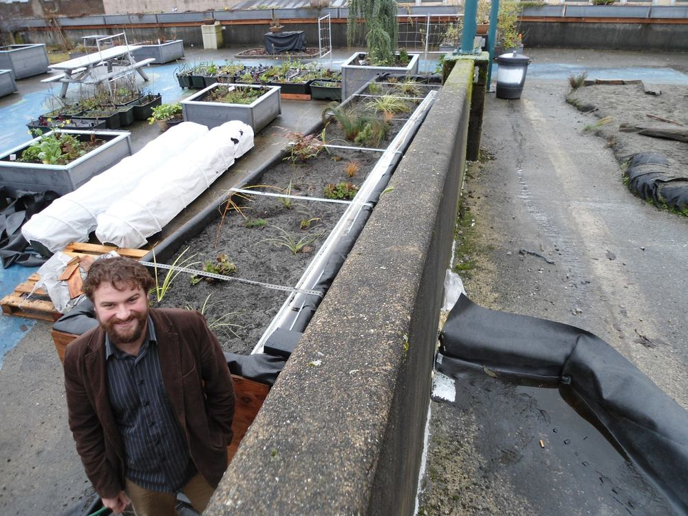 Photo of Derek next to a rooftop rain garden
