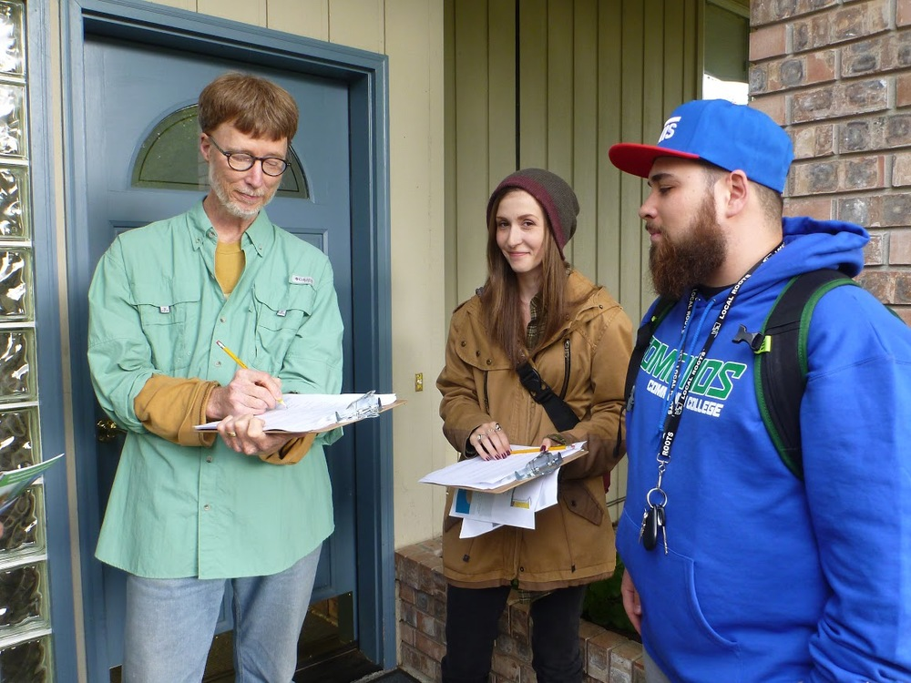 Edmonds Community College students Grace Coale and Blake Caldwell survey homeowner in Perrinville Creek Watershed.