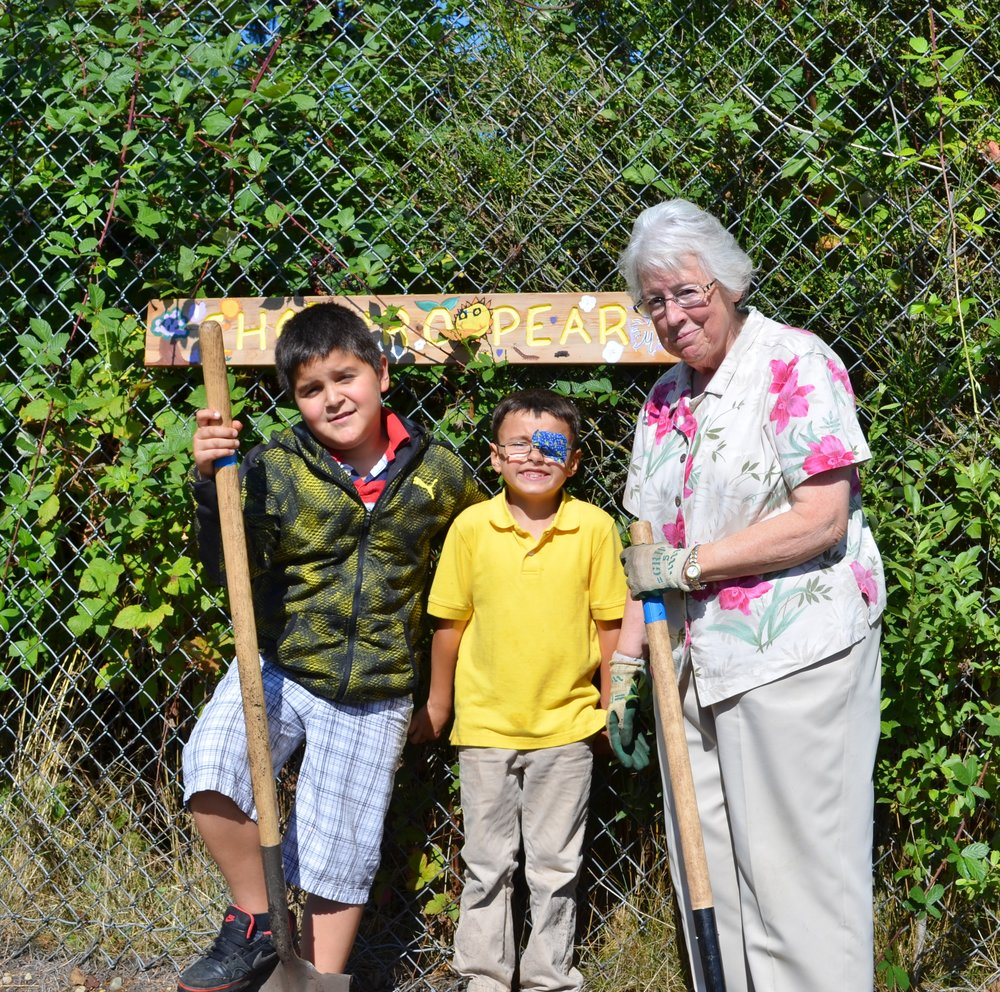 Carlos Aranda poses with a friend and volunteer in the Discovery school garden.