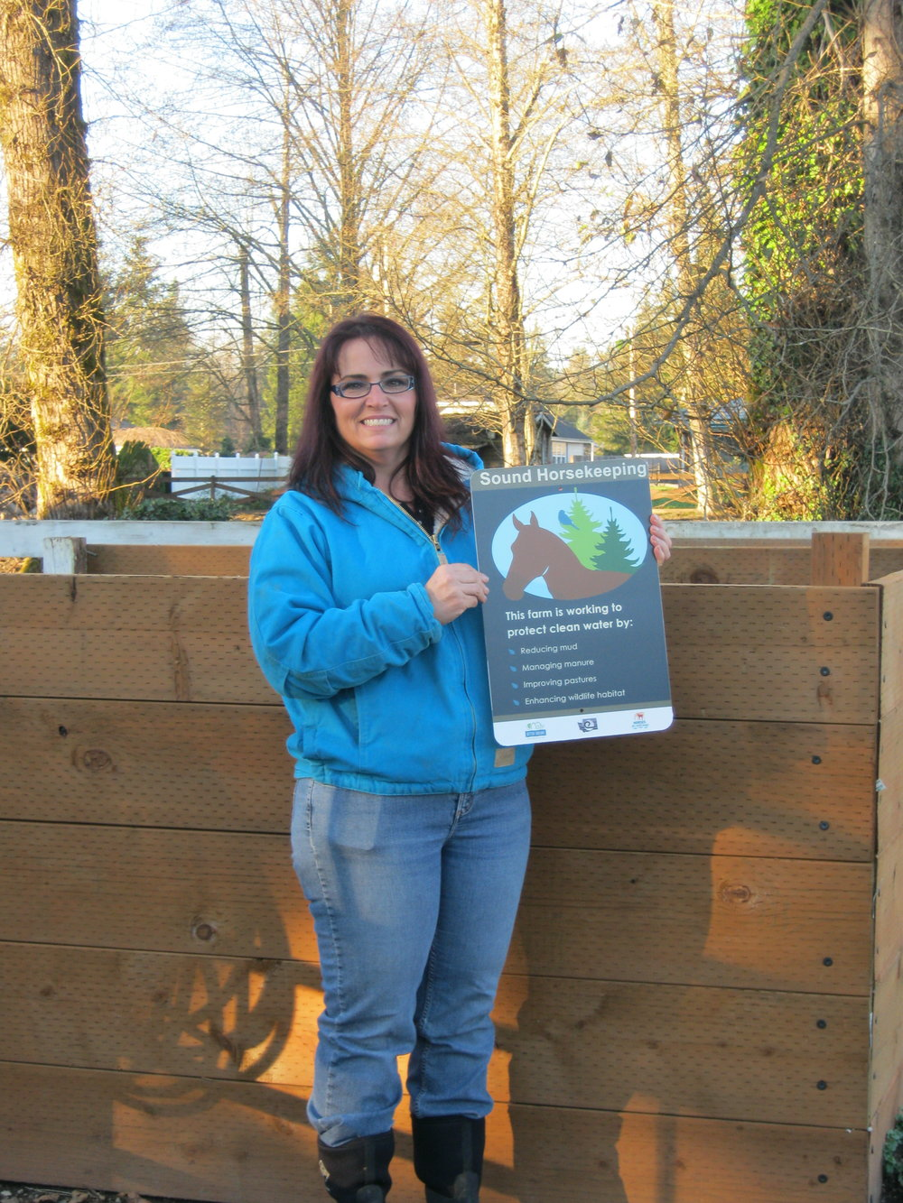 Karen Clark poses with her Sound Horsekeeping sign next to her compost bins