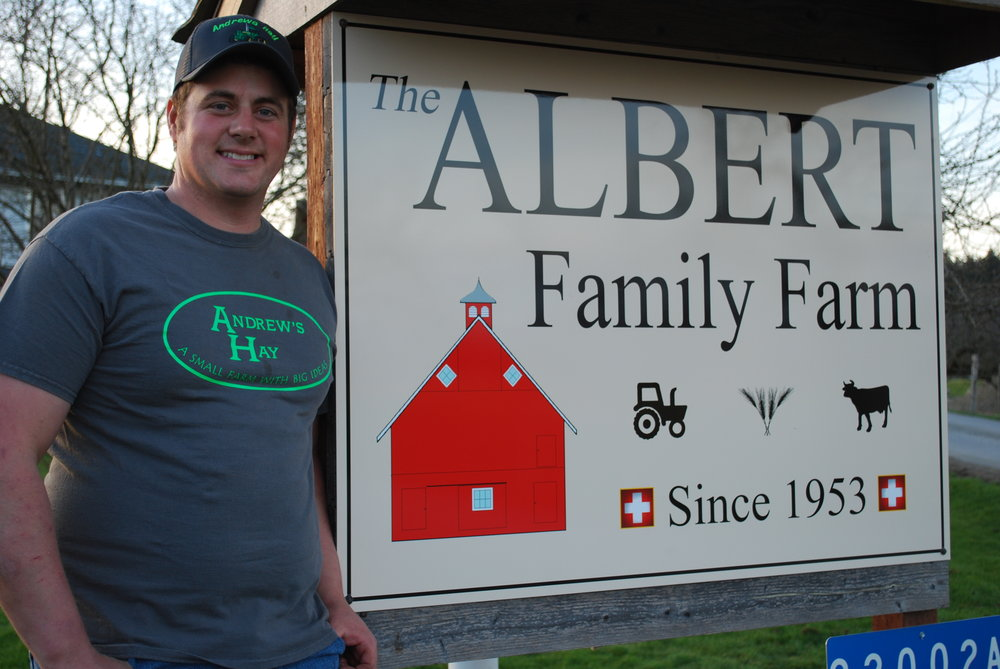 Andrew Albert poses next to his Albert Family Farm sign.